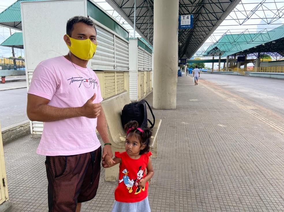 Autônomo Diego Pereira e a filha aguardavam o ônibus nesta segunda-feira em Manaus — Foto: Patrick Marques/G1