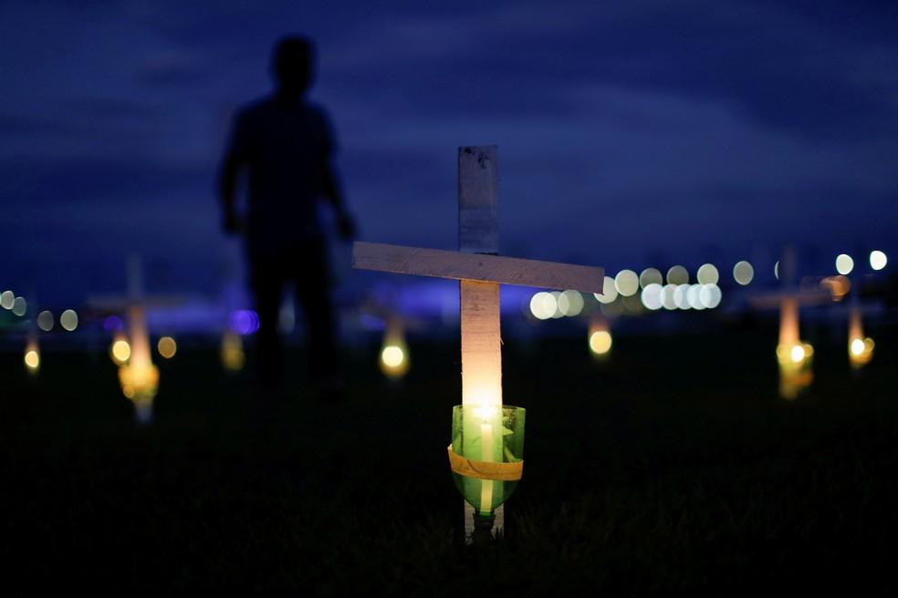 Vela e cruz são colocadas em homenagem às vítimas da Covid-19 em frente ao Congresso, em Brasília, no dia 27 de abril. — Foto: Ueslei Marcelino/Reuters