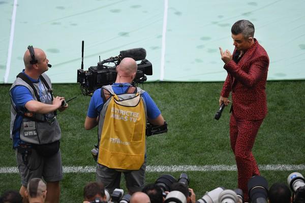 O cantor Robbie Williams mostrando o dedo para uma câmera durante o show de abertura da Copa 2018 (Foto: Getty Images)