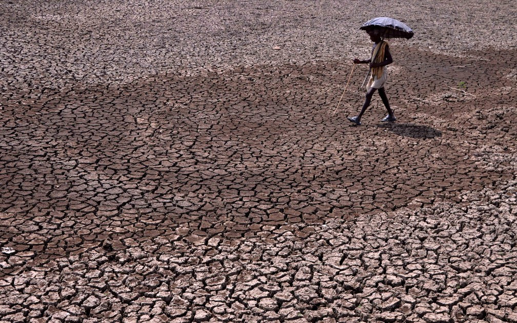 Um homem segura um guarda-chuva ao passar por uma lagoa que secou nos arredores de Bhubaneswar, na Índia. Muitas cidades indianas enfrentam escassez de água no verão, onde as temperaturas passam de 40ºC  — Foto:  Asit Kumar/AFP