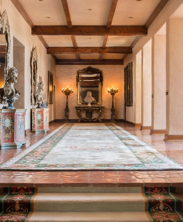 Esculturas decoram a casa que possui corredores abertos e iluminados pela luz natural (Foto: Top Ten Real Estate Deals/ Reprodução)