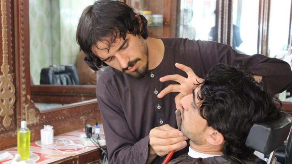 Após a queda do Talibã do poder em 2001, muitos homens passaram a frequentar barbeiros em busca de visual diferente — Foto: Getty Images via BBC