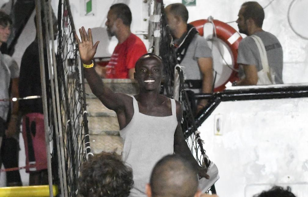 Homem acena ao desembarcar do navio Open Arms na ilha de Lampedusa, na Itália — Foto: AP Photo/Salvatore Cavalli