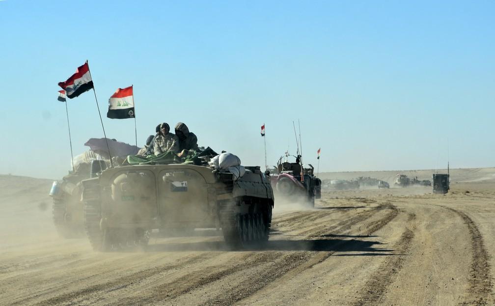 Forças iraquianas e unidades do grupo Hashed al-Shaabi viajam perto da cidade de Qaim, próximo à fronteira com a Síria  (Foto: STRINGER / AFP)