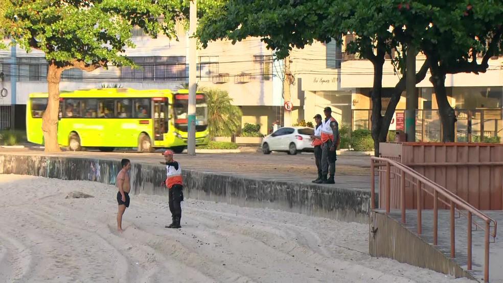 Agentes de segurança orientam pessoas a deixar o calçadão da Praia de Icaraí, na manhã desta quinta-feira (19). — Foto: Reprodução/TV Globo