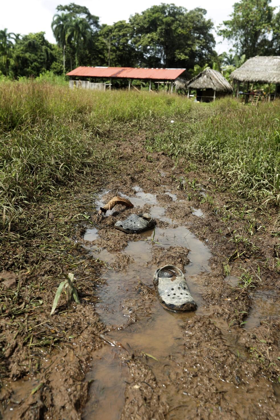 Sandálias foram deixadas em chão lamacento próximo de igreja improvisada onde ritual deixou mortos em El Terrón, no Panamá — Foto: Arnulfo Franco/AP Photo
