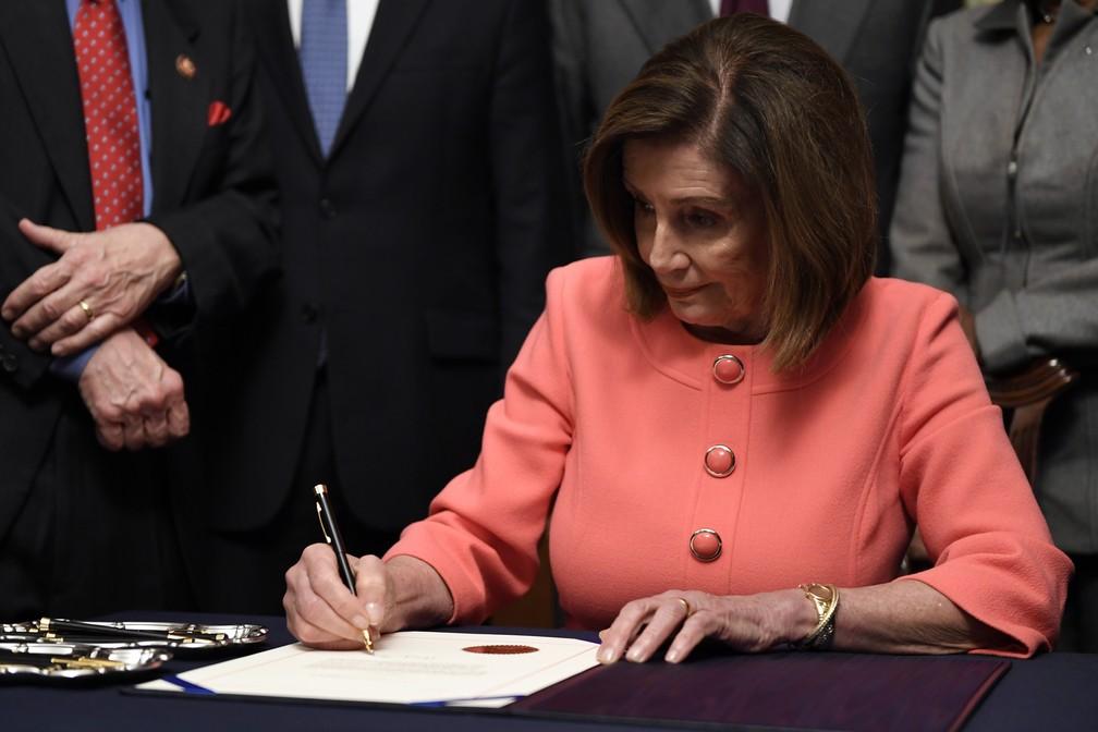 Nancy Pelosi assina documento com artigos de impeachment a ser entregue ao Senado — Foto: AP/Susan Walsh