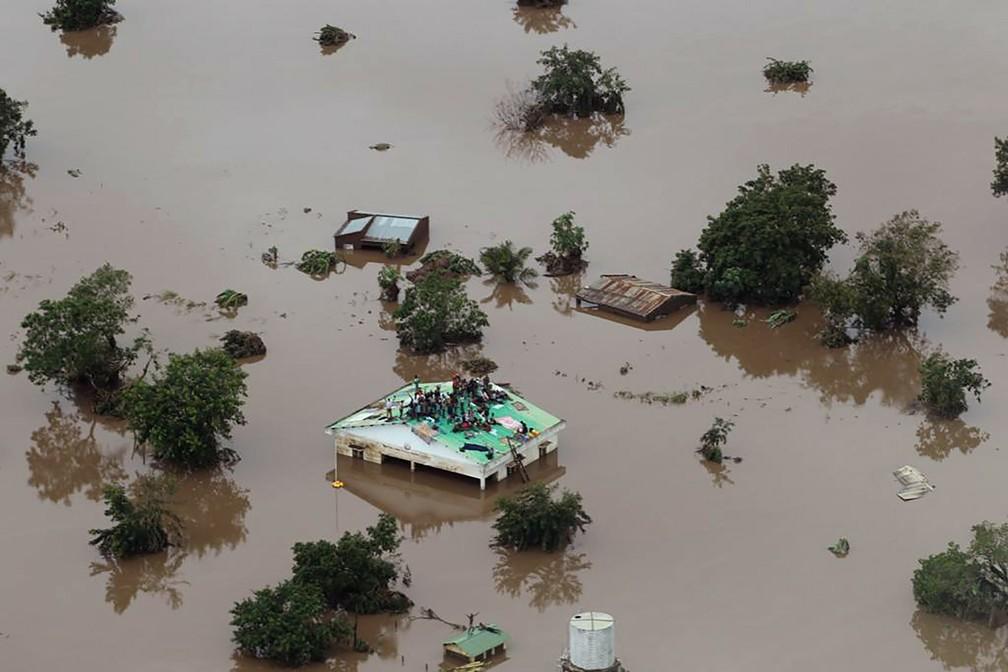 Pessoas se abrigam no teto de uma casa em área completamente alagada após a passagem do ciclone Idai na cidade de Beira, em Moçambique — Foto: Rick Emenaket/Mission Aviation Fellowship via AFP