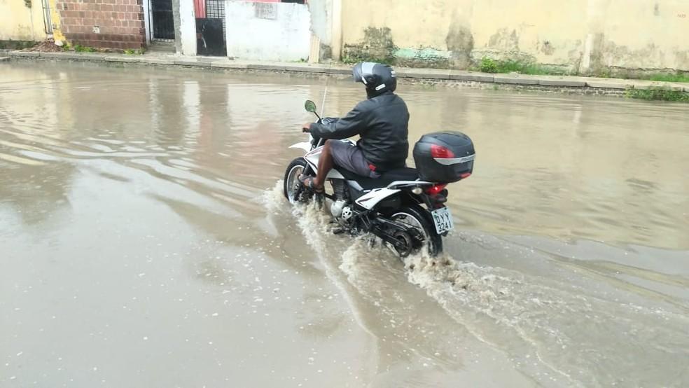 Motociclista passa pela água que alaga a Avenida Pedro Alves Cabral, em Jardim Atlântico, em Olinda, nesta quarta-feira (6) — Foto: Everaldo Silva/TV Globo