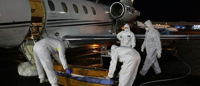 Profissionais de saúde carregam caixão de indígena morto por coronavírus em Manaus