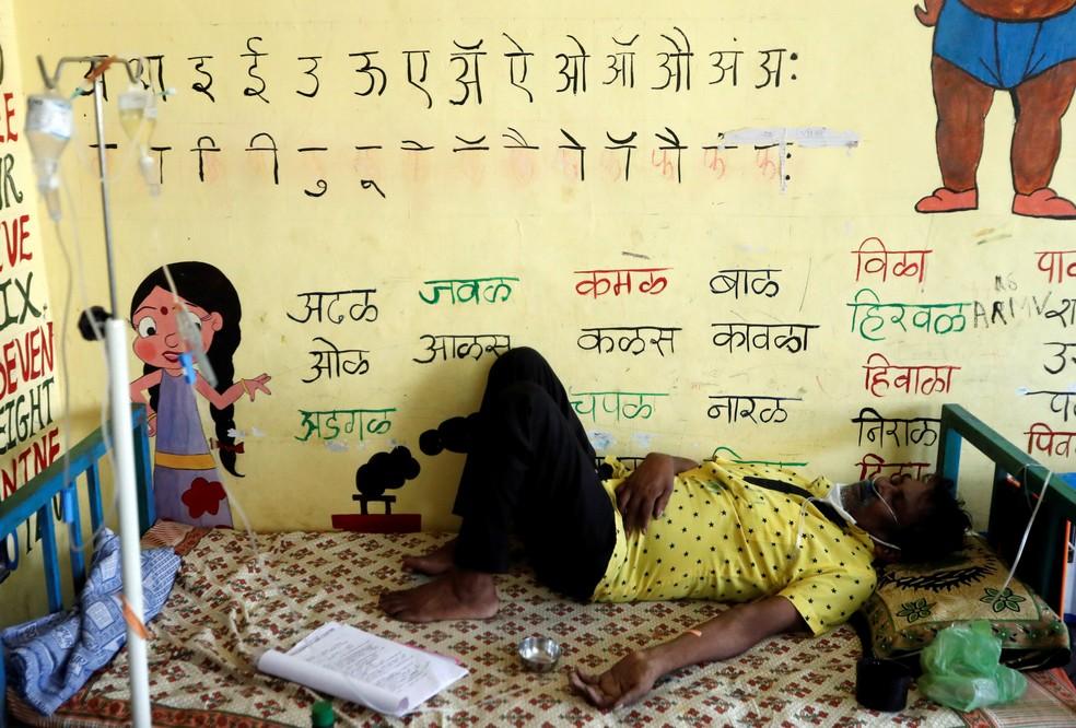 Paciente com Covid-19 recebe suporte de oxigênio enquanto dorme dentro de sala de aula transformada em hospital provisório nos arredores de Mumbai, na Índia, em 24 de maio — Foto: Francis Mascarenhas/Reuters