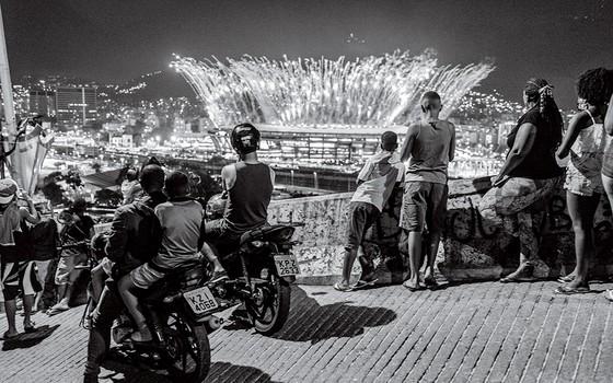 Os moradores da Mangueira assistem de sua comunidade os fogos de artifício durante a cerimônia de abertura dos Jogos Olímpicos de 2016 no Rio de Janeiro (Foto: João Pina)