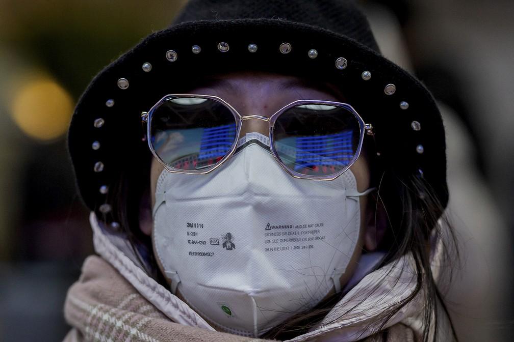 Mulher usa máscara de proteção contra o coronavírus no saguão de entrada da estação de trem de Pequim em 24 de janeiro — Foto: Nicolas Asfouri/AFP