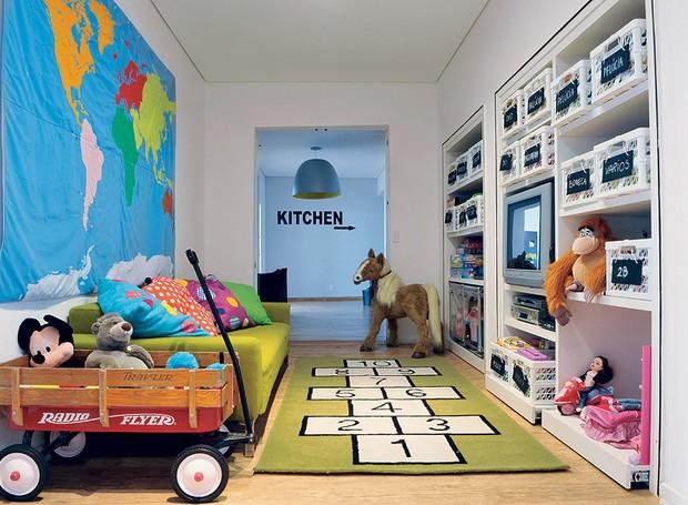 A arquiteta Valéria Blay arrancou as portas do armário, manteve as prateleiras e transformou o móvel em uma estante para brinquedos. Sofá, tapete divertido e TV foram bem-vindos e o amplo corredor virou um espaço para brincar (Foto: Marcelo Magnani/Casa e Jardim)