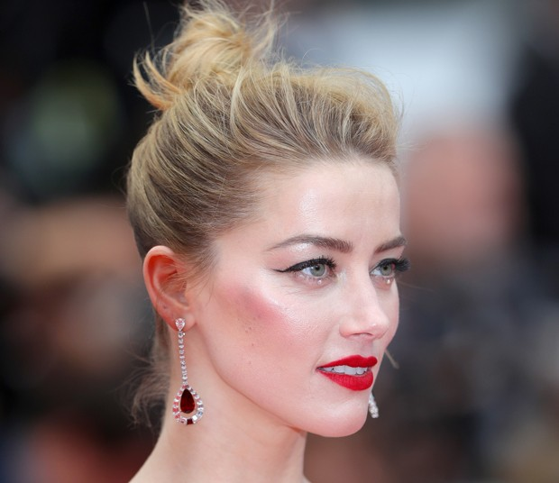 Amber Heard apostou no combo delineador estilo gatinho e lábios vermelhos. Destaque para o brilho aplicado em baixo dos olhos (Foto: Getty Images)