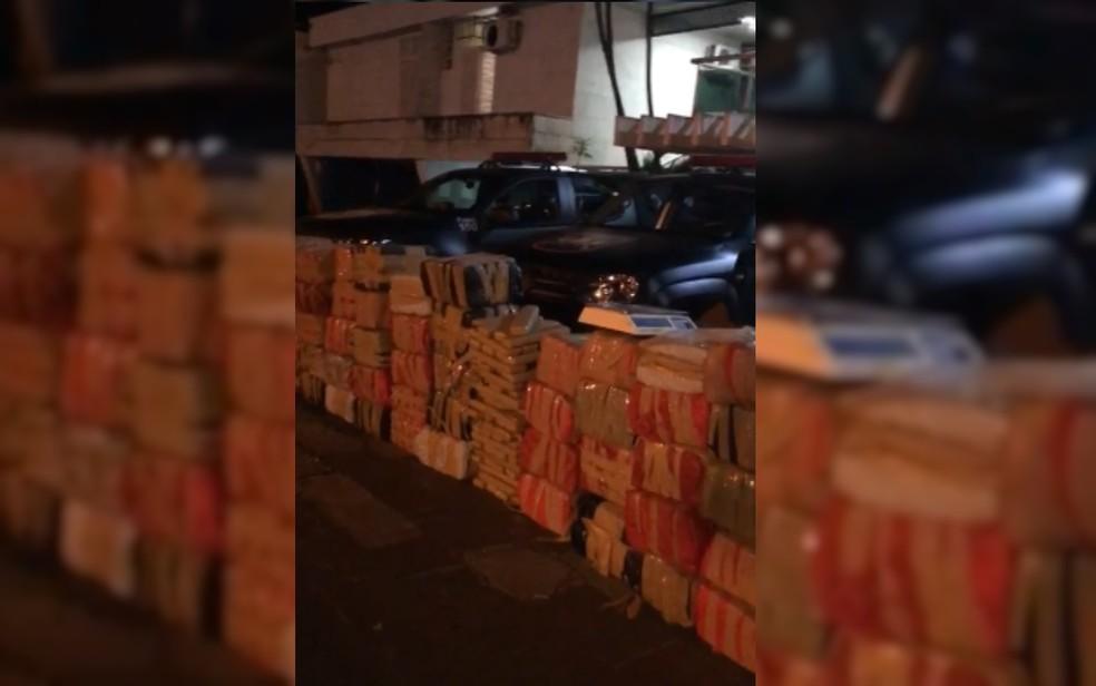 Pacotes de maconha apreendidos em caminhão-baú quebrado e fazenda na zona rural de Pirenópolis, em Goiás, com balança usada para pesá-los; ao fundo, carros da Polícia Militar (Foto: Polícia Militar/Divulgação)
