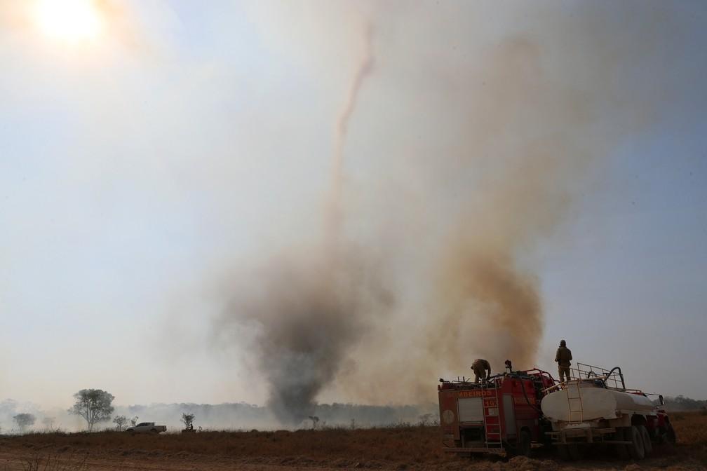 Bombeiros do Estado de Mato Grosso abastecem seu caminhão com água enquanto se preparam para apagar um incêndio em frente a um funil de fumaça em uma fazenda no Pantanal — Foto: Amanda Perobelli/Reuters