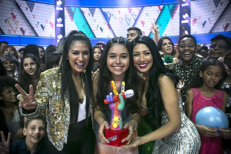"""Eduarda Brasil, vencedora da terceira temporada do """"The Voice Kids"""", entre as técnicas Simone e Simaria  — Foto: Divulgação/TV Globo"""