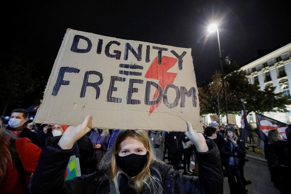 'Dignidade = liberdade', diz cartaz de manifestante que foi às ruas de Varsóvia nesta sexta (30) em protesto contra medida que endurece regras do aborto na Polônia — Foto: Kacper Pempel/Reuters