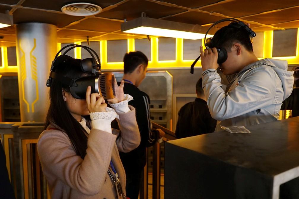 Visitantes usam óculos de realidade virtual em parque temático na província Guizhou, na China. (Foto: Joseph Campbell/Reuters)