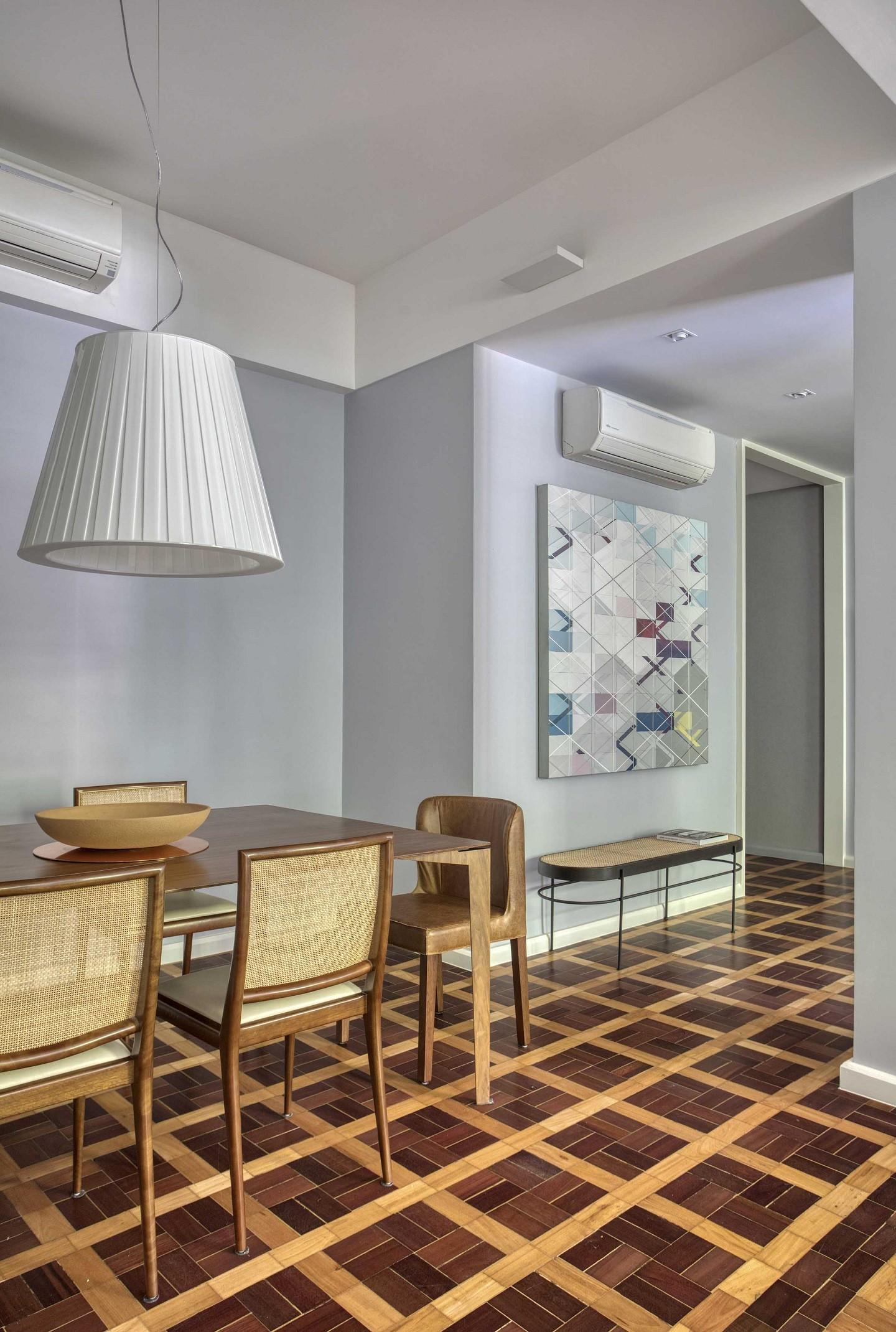 Ambiente com piso de taco, mesa e cadeiras de madeira, quadro e luminária pendente.