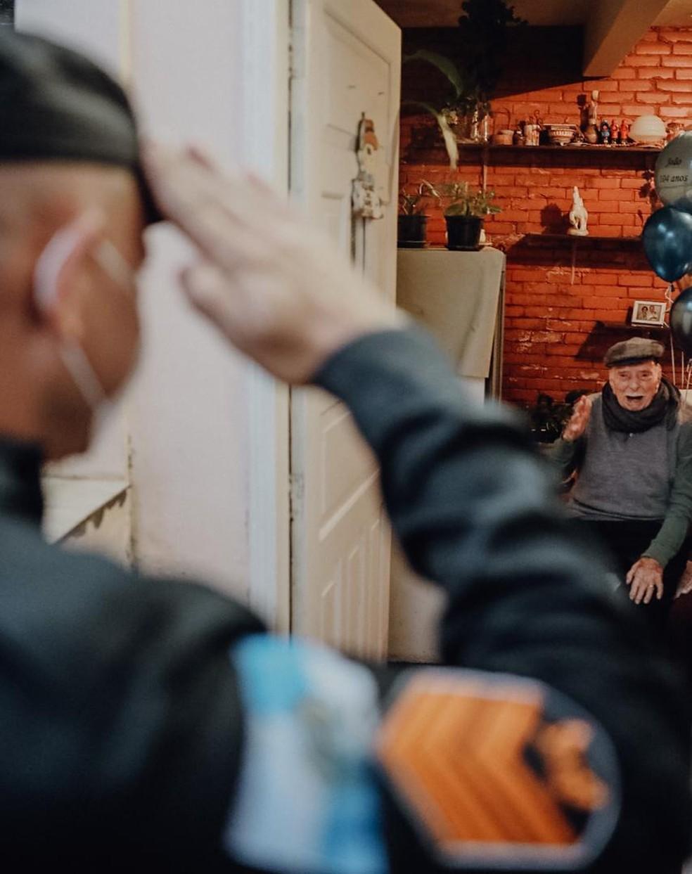João Freire Jucá Sobrinho atuou durante 40 anos na Polícia Militar. Ele recebeu continência de representante da PM durante seu aniversário de 104 anos em Petrópolis — Foto: Giovani Garcia