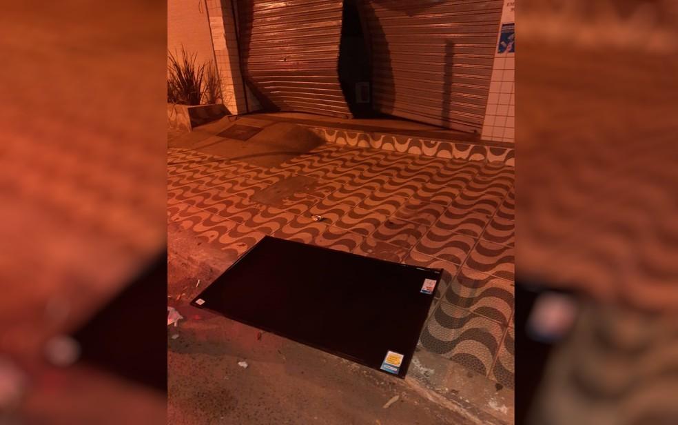 Ao fugir, os criminosos deixaram uma televisão na calçada — Foto: Polícia Militar/Divulgação