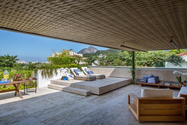 PISCINA | As espreguiçadeiras, a poltrona e o sofá no canto direito são da Pátio Brasil. A mesa de refeição é da Arquivo Contemporâneo. A cadeira é a ICZERO1, assinada por Guto Indio da Costa e vendida pela Novo Ambiente. O banco de madeira próximo à piscina é da Arquivo Contemporâneo. (Foto: Juliano Colodeti / MCA Estúdio)