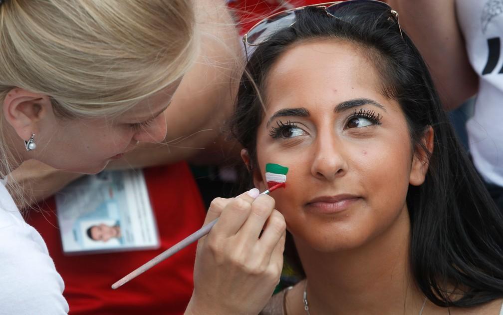 Mulher pinta rosto de torcedora iraniana em estádio de São Petersburgo durante jogo entre Irã e Marrocos na Copa do Mundo da Rússia, na sexta-feira (15) — Foto: AP Photo/Dmitri Lovetsky