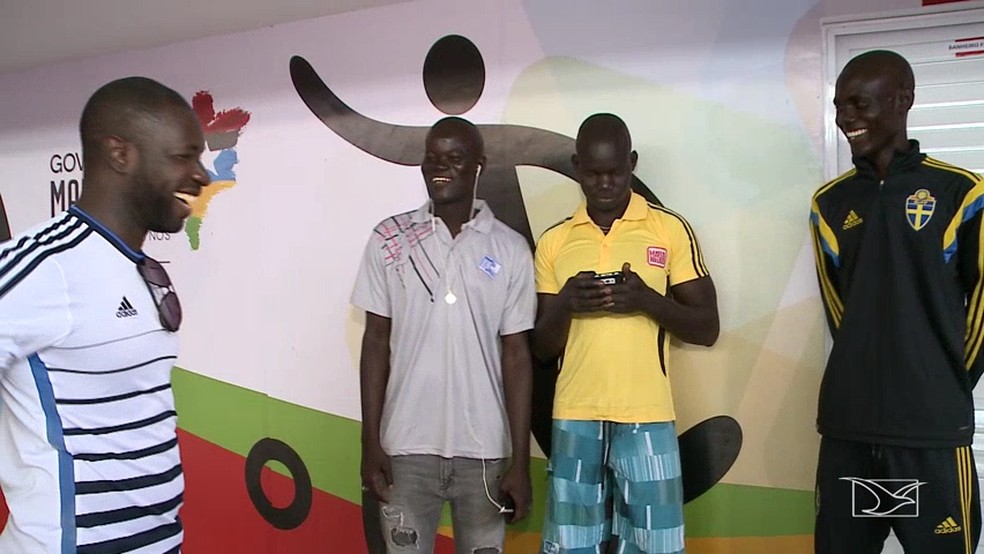 Marcelino Soares (primeiro à esquerda) conversa com alguns dos africanos resgatados no Maranhão (Foto: Reprodução/TV Mirante)
