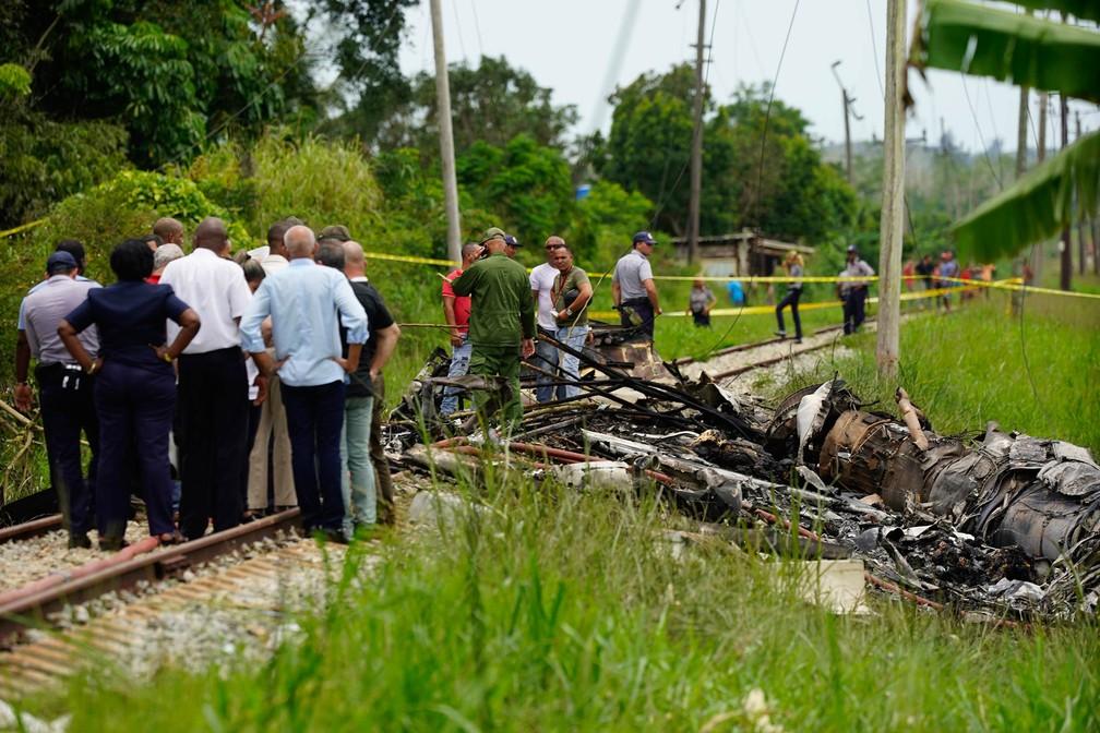 Equipe de resgate e busca trabalha entre destroços de avião que pararam sobre trilhos de uma rodovia após acidente aéreo em Havana (Foto: Ramon Espinosa/AP)