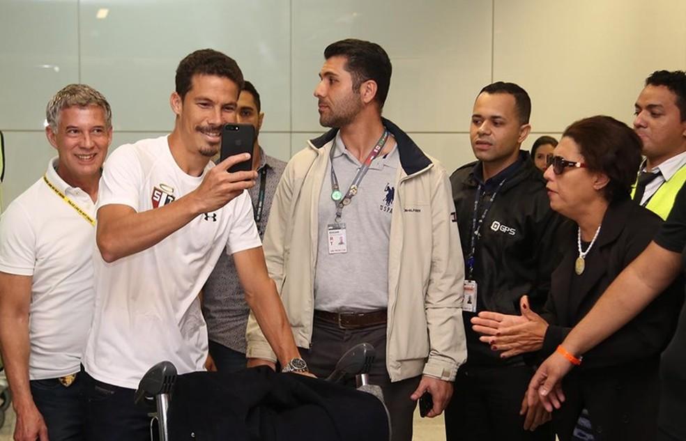 Hernanes filma chegada no saguão de Cumbica (Foto: Rubens Chiri/Saopaulofc.net)