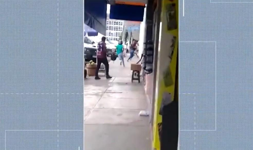 Vídeo flagrou um dos suspeitos, de verde, correndo após assalto — Foto: Reprodução/TV Santa Cruz