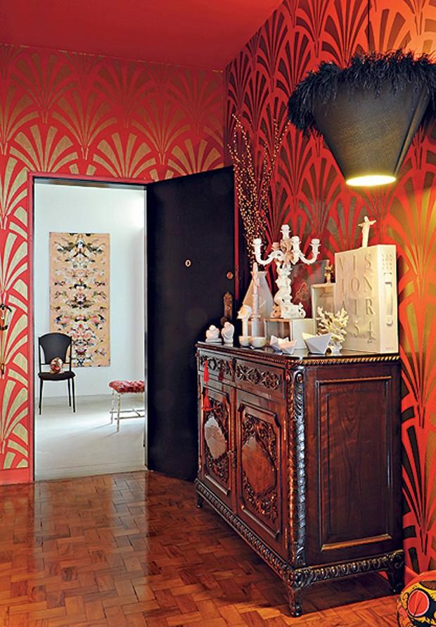Tudo da mesma cor neste hall. O arquiteto César Aumart concentrou as peças brancas sobre o aparador de madeira escura. A coleção ganhou destaque com a pintura das paredes com tinta vermelho-cereja e a aplicação de adesivos dourados em forma de leque (Foto: Arquivo Casa e Jardim)