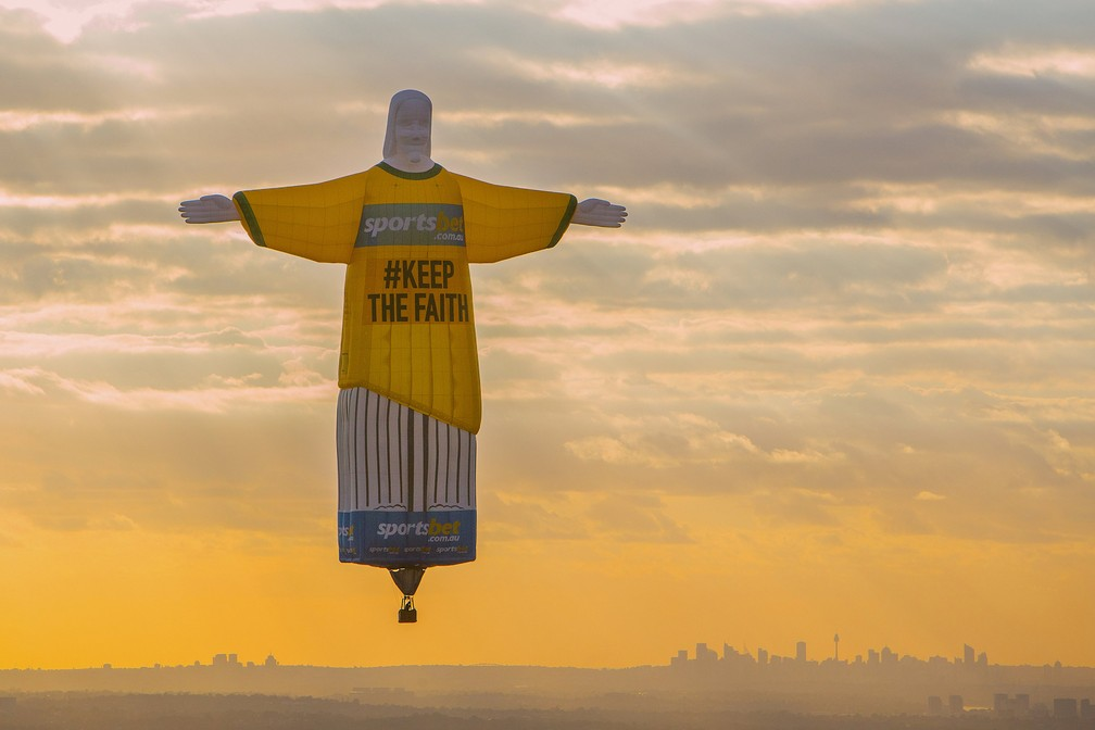 -  Um balão no formato da estátua do Cristo Redentor é vista no céu de Sydney como parte de uma campanha publicitária, na Austrália  Foto: Steve Christo