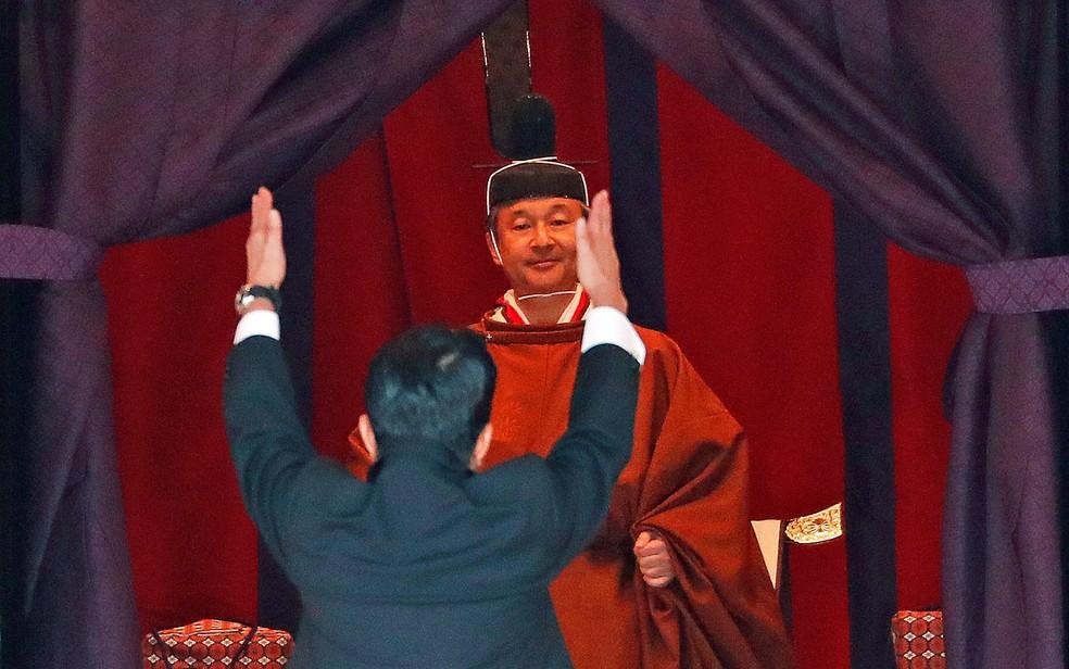 "O primeiro-ministro do Japão, Shinzo Abe, levanta as mãos enquanto grita ""banzai"" o novo imperador Naruhito — Foto: Issei Kato / Pool / via AP Photo"
