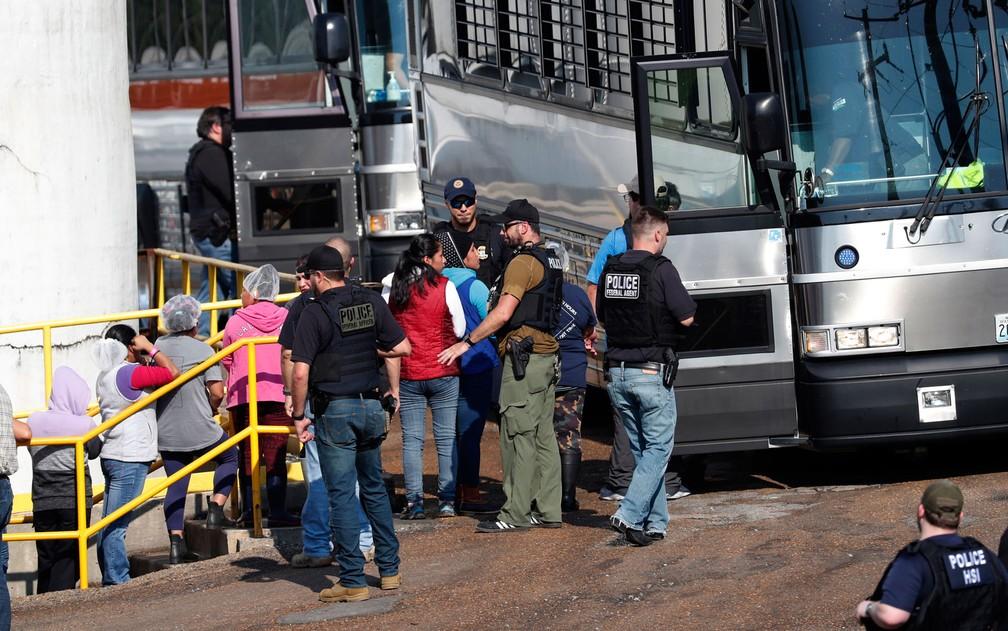 Funcionárias algemadas são escoltadas até ônibus por agentes de imigração em fábrica da Koch Foods Inc. em Morton, Mississippi, na quarta-feira (7) — Foto: AP Photo/Rogelio V. Solis