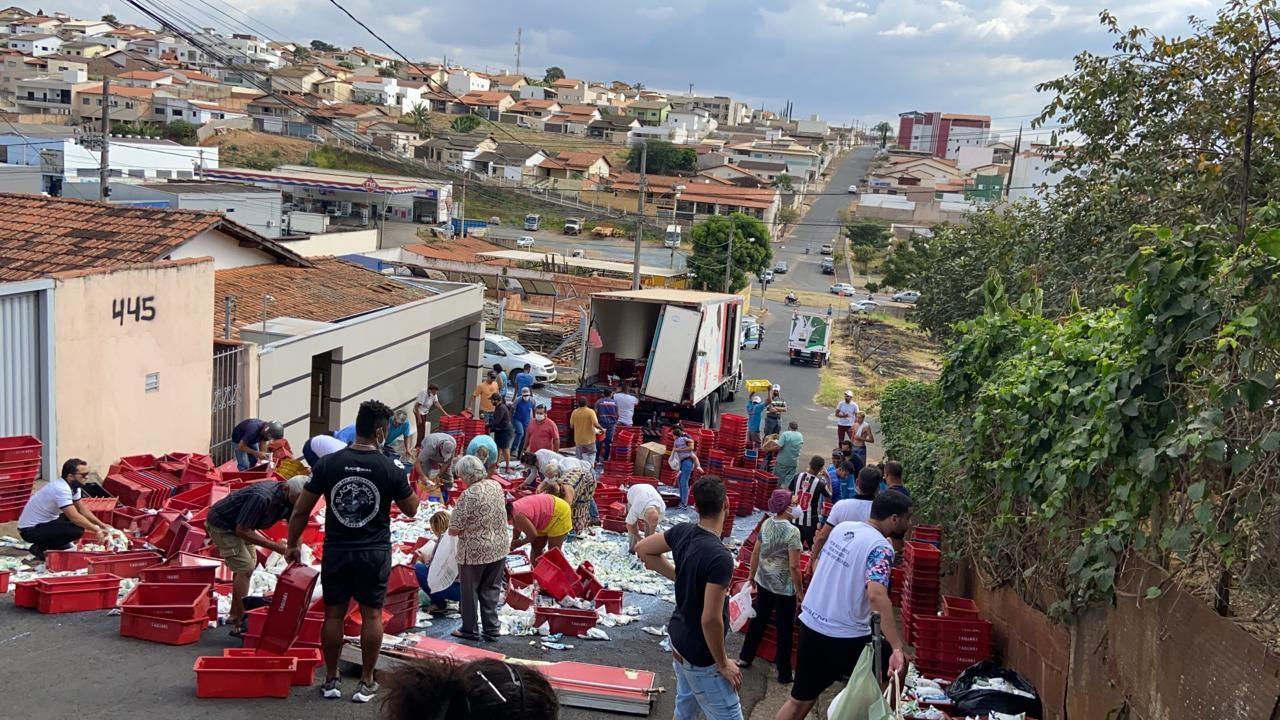 Porta traseira de caminhão se rompe e carga com laticínios cai no meio da rua em Araxá; moradores saquearam pacotes de leite e queijos