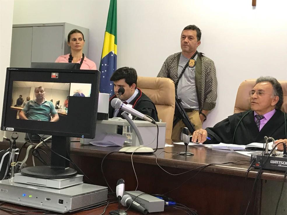 No monitor, Cesare Battisti, e à direita, o juiz federal Odilon de Oliveira durante audiência de custódia por videoconferência na Justiça Federal em MS (Foto: Claudia Gaigher/TV Morena)