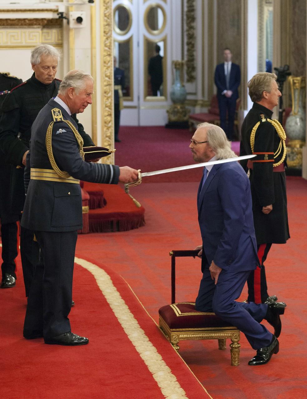 O cantor Barry Gibb, do grupo Bee Gees, é condecorado pelo príncipe Charles e recebe título de cavaleiro do Palácio de Buckingham (Foto: Dominic Lipinski/PA via AP)