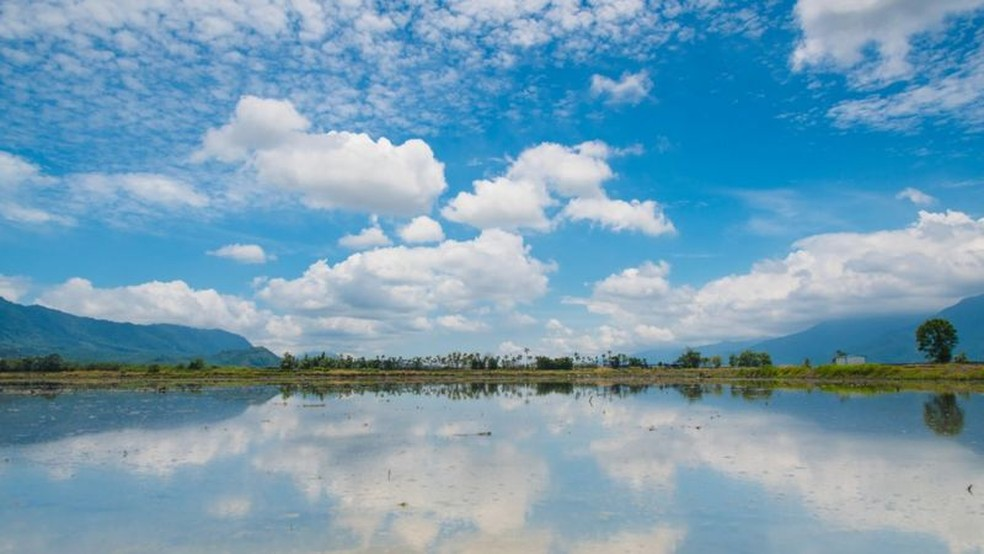 Campo de arroz em Taiwan: sob um céu azul com nuvens, um campo alagado refletindo a paisagem — Foto: Getty Images via BBC