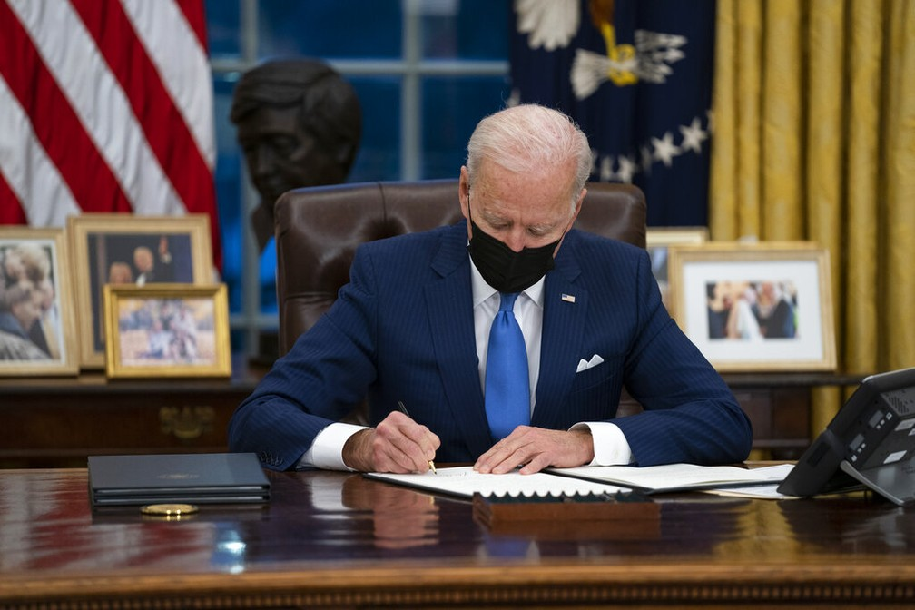 Presidente dos EUA, Joe Biden, assina decretos sobre imigração no Salão Oval da Casa Branca nesta terça-feira (2) — Foto: Evan Vucci/AP Photo