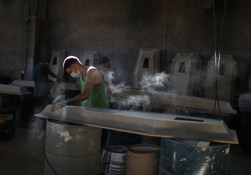 Trabalhador prepara caixão em fábrica em Nova Iguaçu, no Rio de Janeiro, em 12 de abril em meio à pandemia do novo coronavírus no Brasil — Foto: Pilar Olivares/Reuters