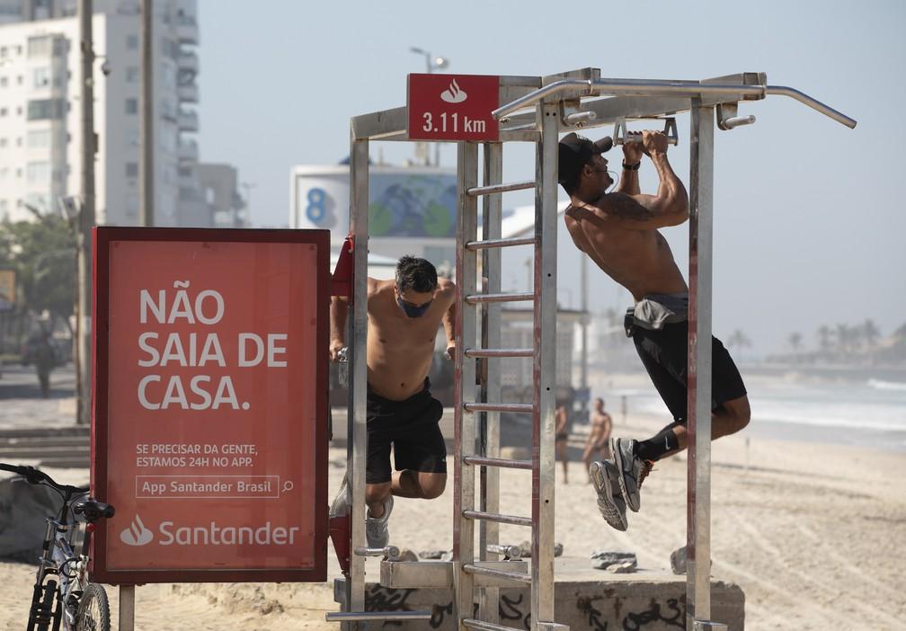 Homens se exercitam em equipamento de ginástica no calçadão da praia de Ipanema — Foto: Silvia Izquierdo/AP
