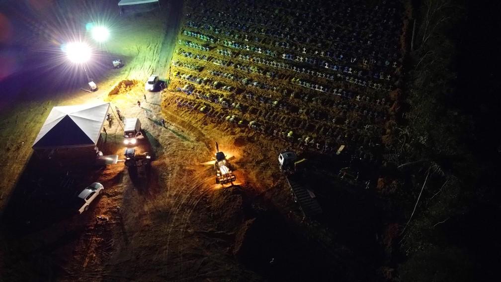 Refletores iluminam caixões e máquinas para enterros em massa, em Manaus. — Foto: Chico Batata/Divulgação