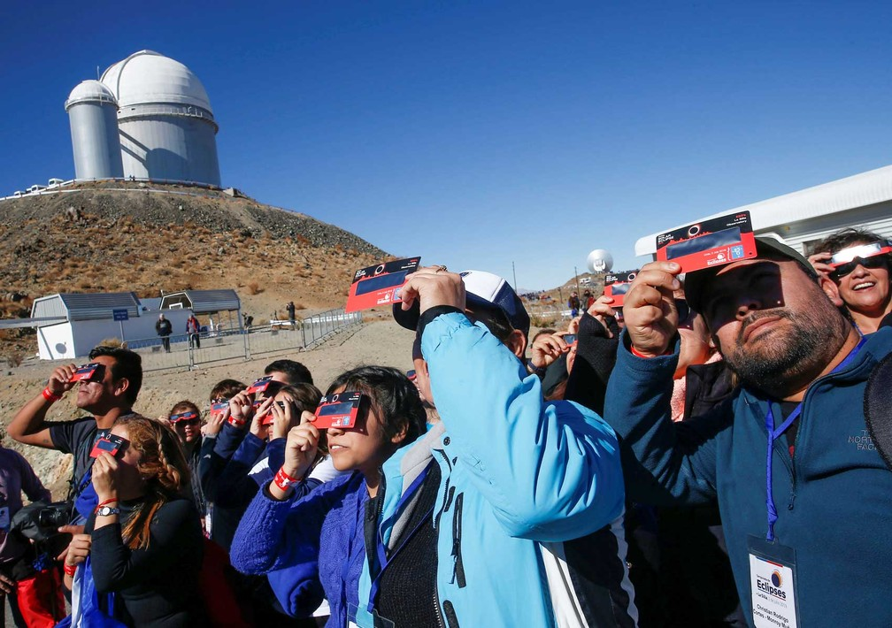Antes do eclipse, visitantes do Observatório de La Silla testam seus óculos especiais para ver o eclipse. — Foto: Rodrigo Garrido/Reuters