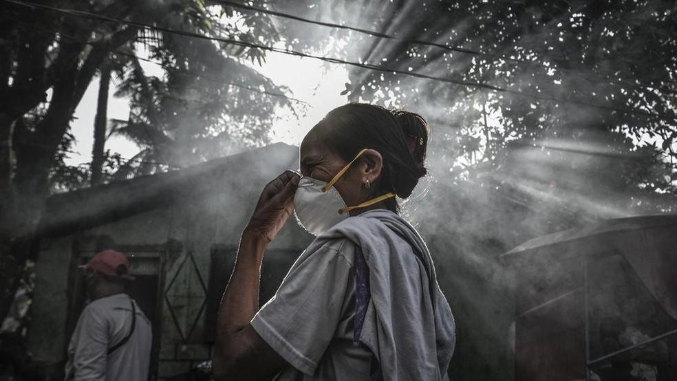 As pessoas que moram perto do Monte Mayon, nas Filipinas, precisaram de máscaras quando ele entrou em erupção em janeiro de 2018 (Foto: Getty Images/ via BBC)