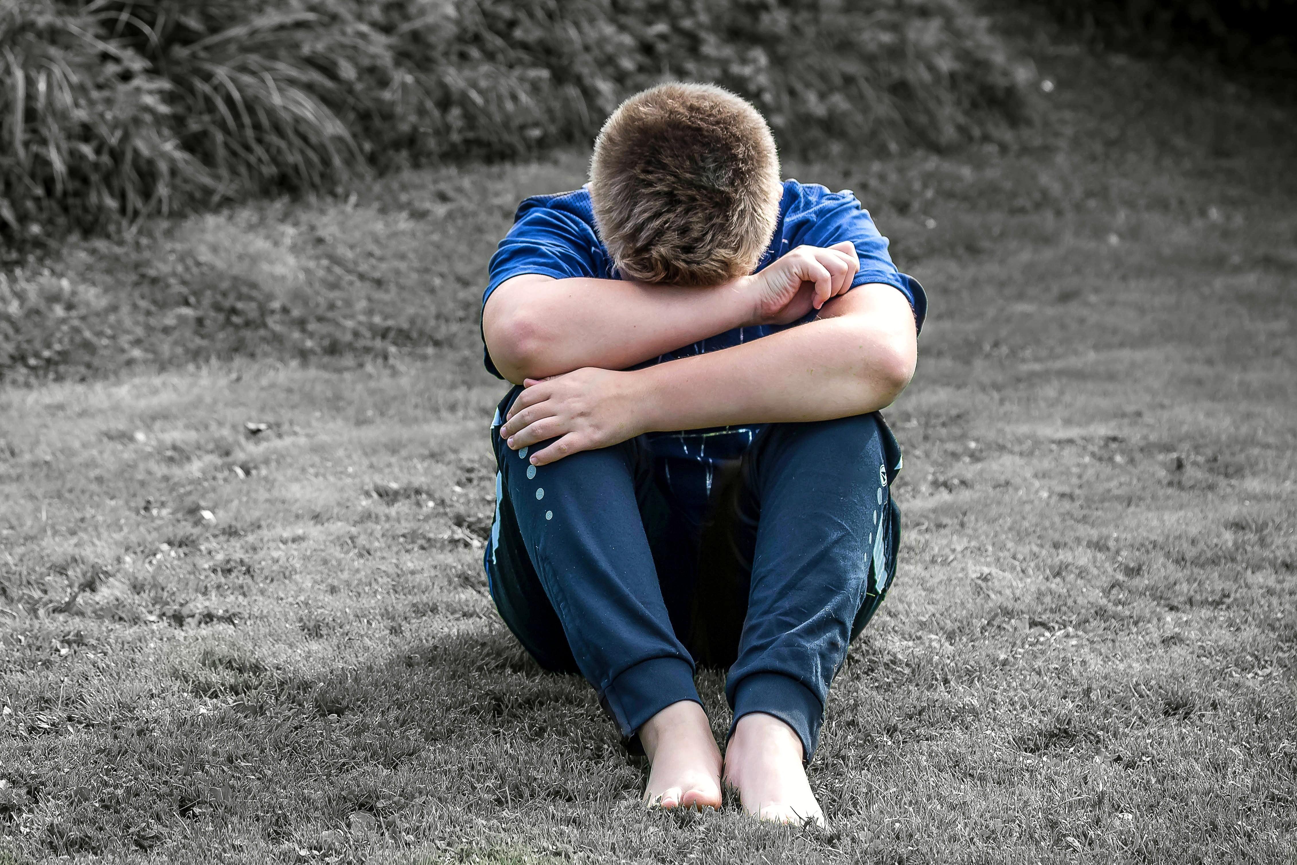 Menino sentado na grama e encolhido (Foto: Pixabay/Pexels)