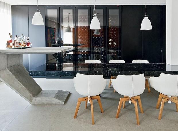 Com a redução da cozinha, que recortava parte do living, os arquitetos Paula Zemel e Eduardo Chalabi conseguiram espaço para instalar uma adega climatizada voltada para a sala de jantar. Ela fica em painel preto, que camufla a porta do lavabo (Foto: Maíra Acayaba/Casa e Jardim)