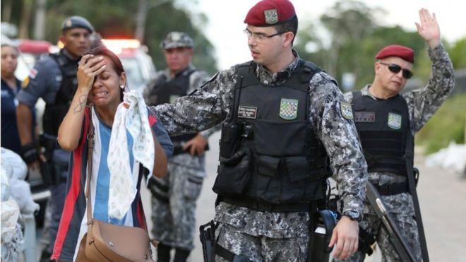 Policial consola parente de preso em presídio de Manaus; para socióloga, sociedade não tem empatia pela população carcerária (Foto: Reuters, via BBC)
